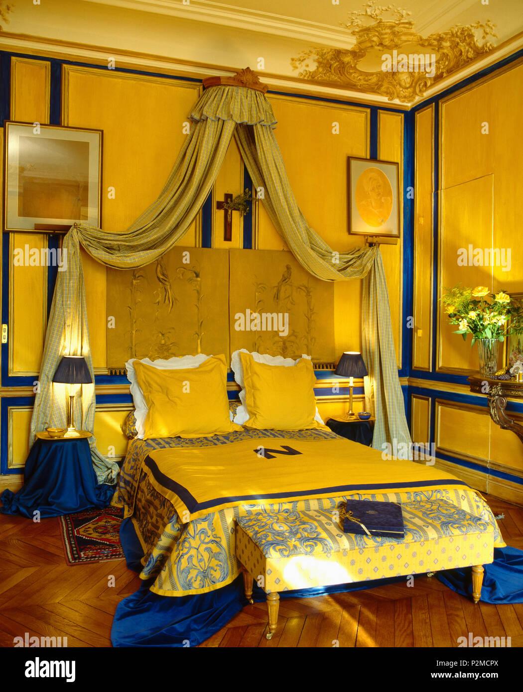 Coronet avec rideaux crème au-dessus de lit avec couvre-lit bleu + ...