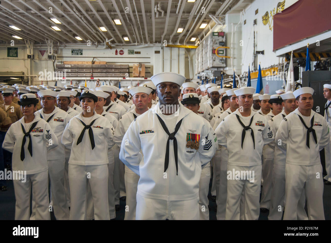 160804-N-EW322-033 SAN DIEGO (Août 4, 2016) - 1ère classe Mécanicien structurels de l'Aviation Jamaan Fripp, de Beaufort, Caroline du Sud, est en formation avec ses collègues USS Makin Island (DG 8) marins au cours d'une cérémonie de passation de commandement dans le hangar du navire. Capt Mark Melson soulagé le Capitaine Jon P. Rodgers durant la cérémonie. Le navire d'assaut amphibie est homeported à San Diego. (U.S. Photo par marine Spécialiste de la communication de masse Seaman Clark D. Lane/libérés) Photo Stock