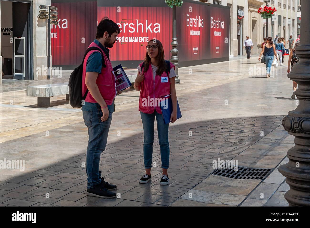 Deux 'charité' chuggers parlent entre eux sur la rue commerçante principale de Malaga à Malaga, Espagne. Photo Stock
