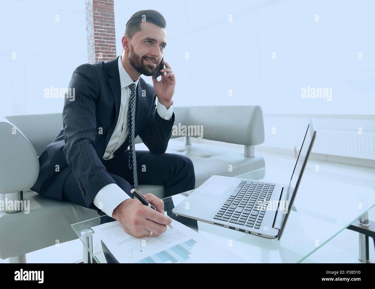 Businessman talking on smartphone à propos de documents financiers Photo Stock