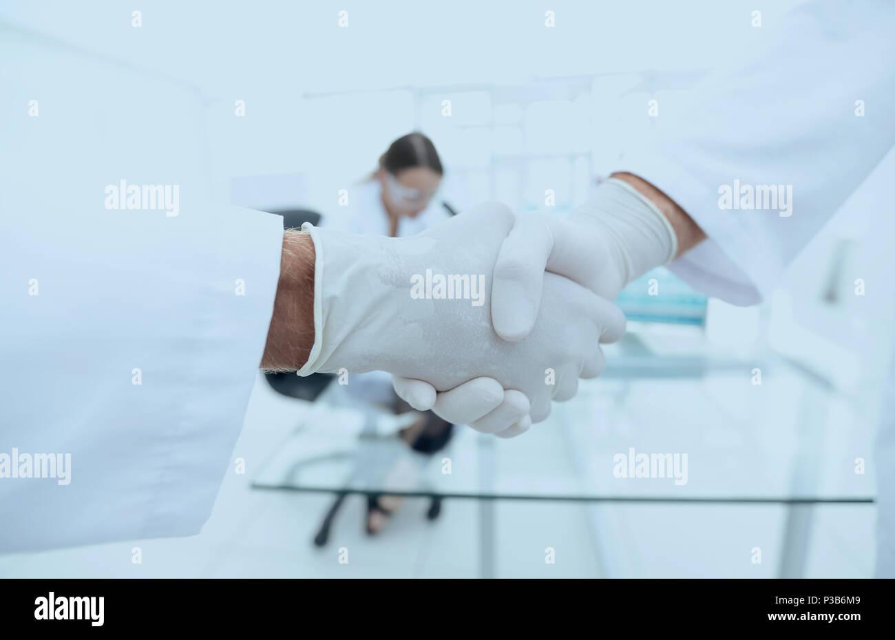 Les médecins en sarrau chaque message d'autres avec handshake Banque D'Images