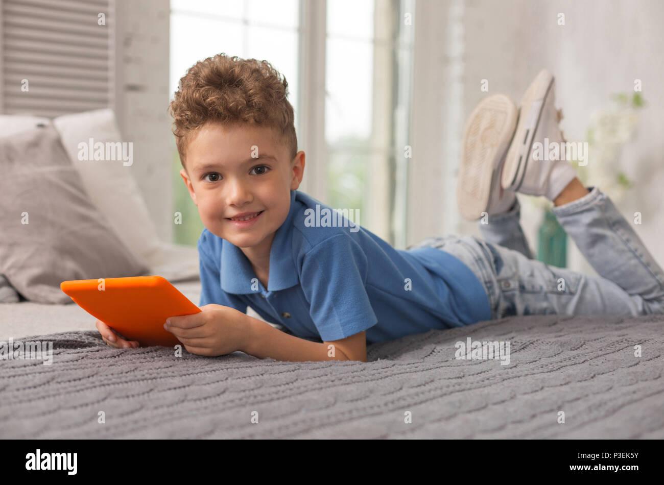 Smiling adorable garçon couché sur un lit double Photo Stock
