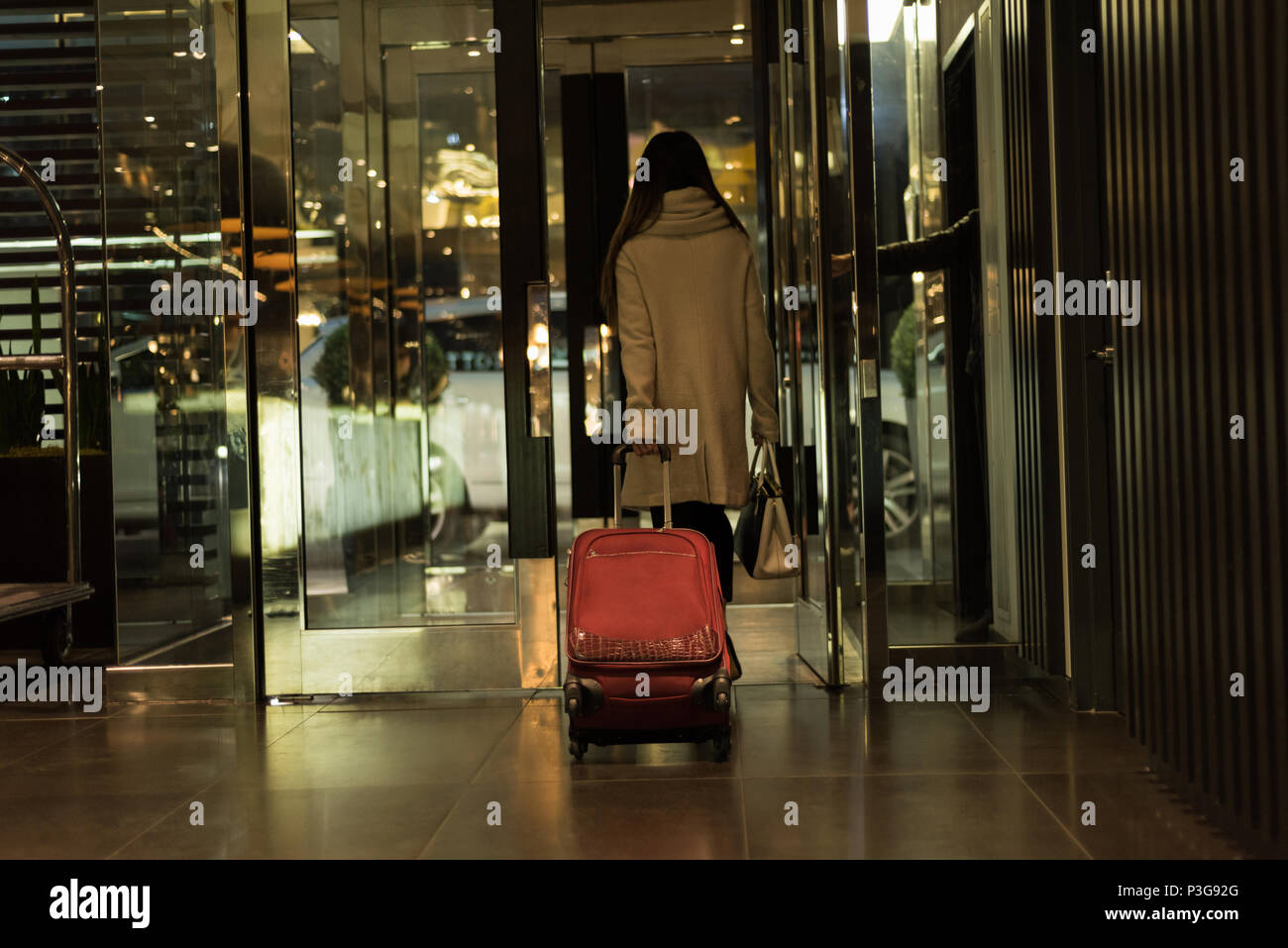 Businesswoman walking out de la chambre d'hôtel avec les bagages Photo Stock