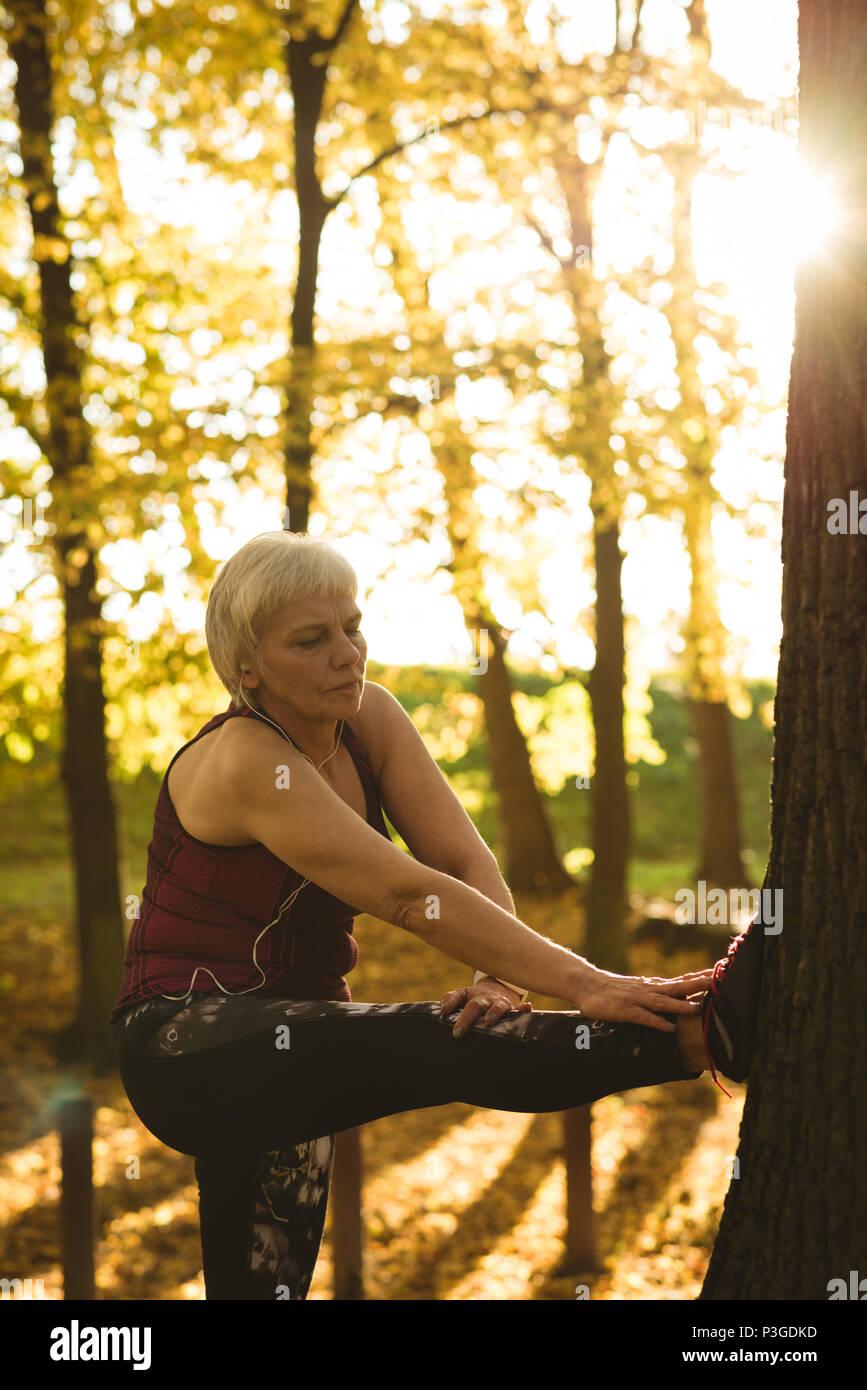 Senior woman performing exercice s'étendant dans le parc Photo Stock
