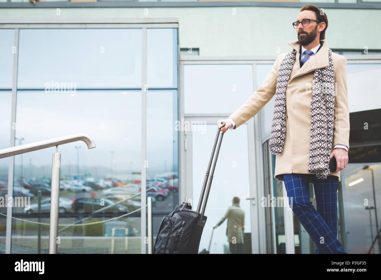 Businessman standing avec sac voyage à roulettes Photo Stock