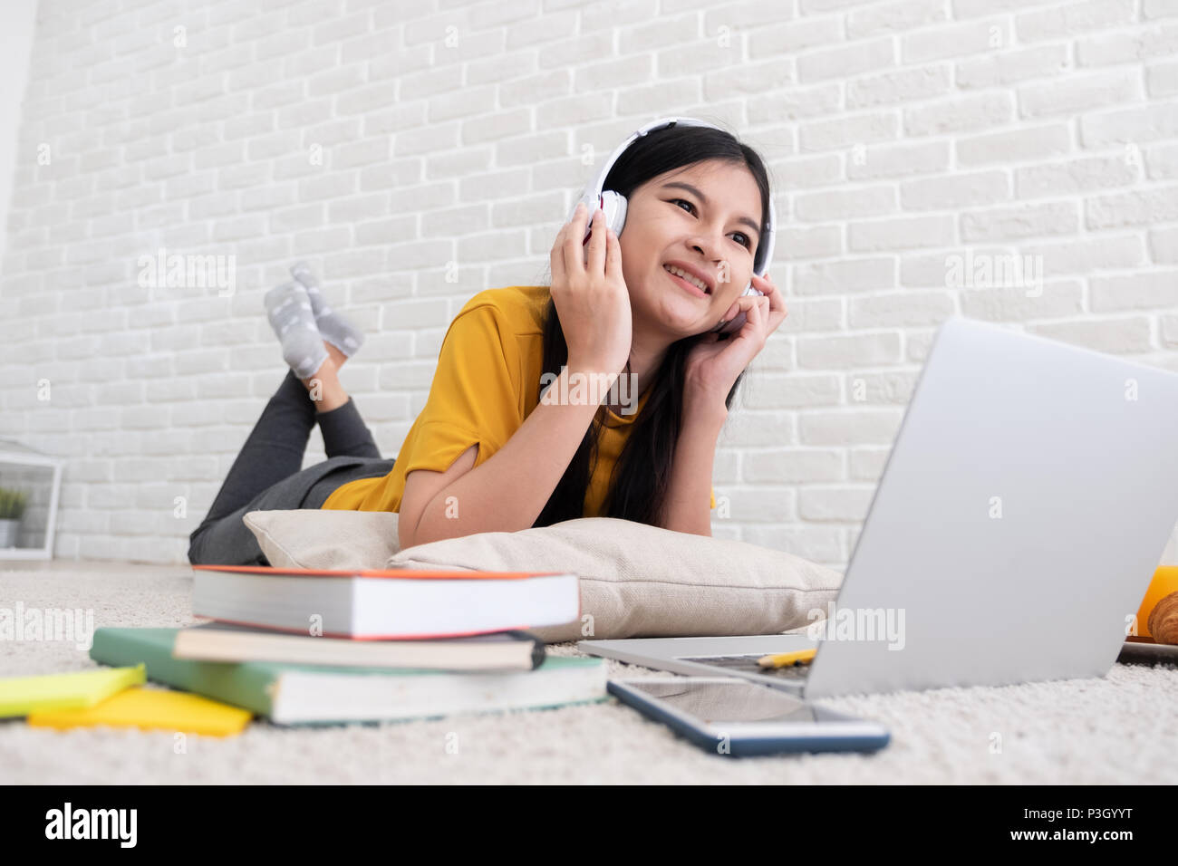 Femme d'origine asiatique d'écouter de la musique et utiliser un ordinateur portable pour travailler à la maison.femme se coucha sur tapis en mur de briques.en ligne de mode de travail Photo Stock