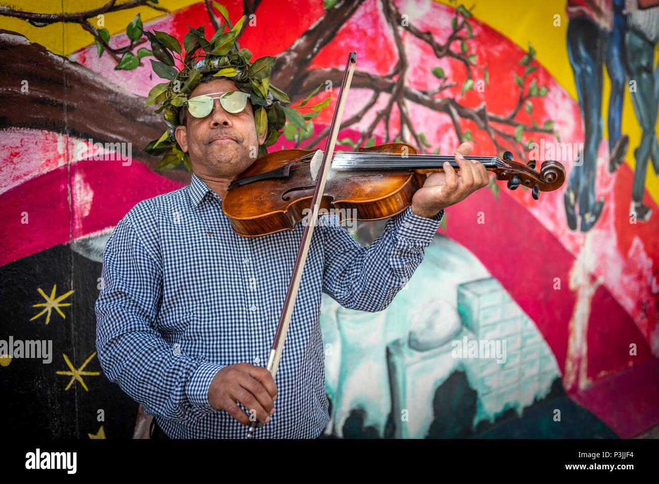 Un musicien ambulant divertit les touristes sur le site du Mur de Berlin, en ex-Allemagne de l'Est. Banque D'Images