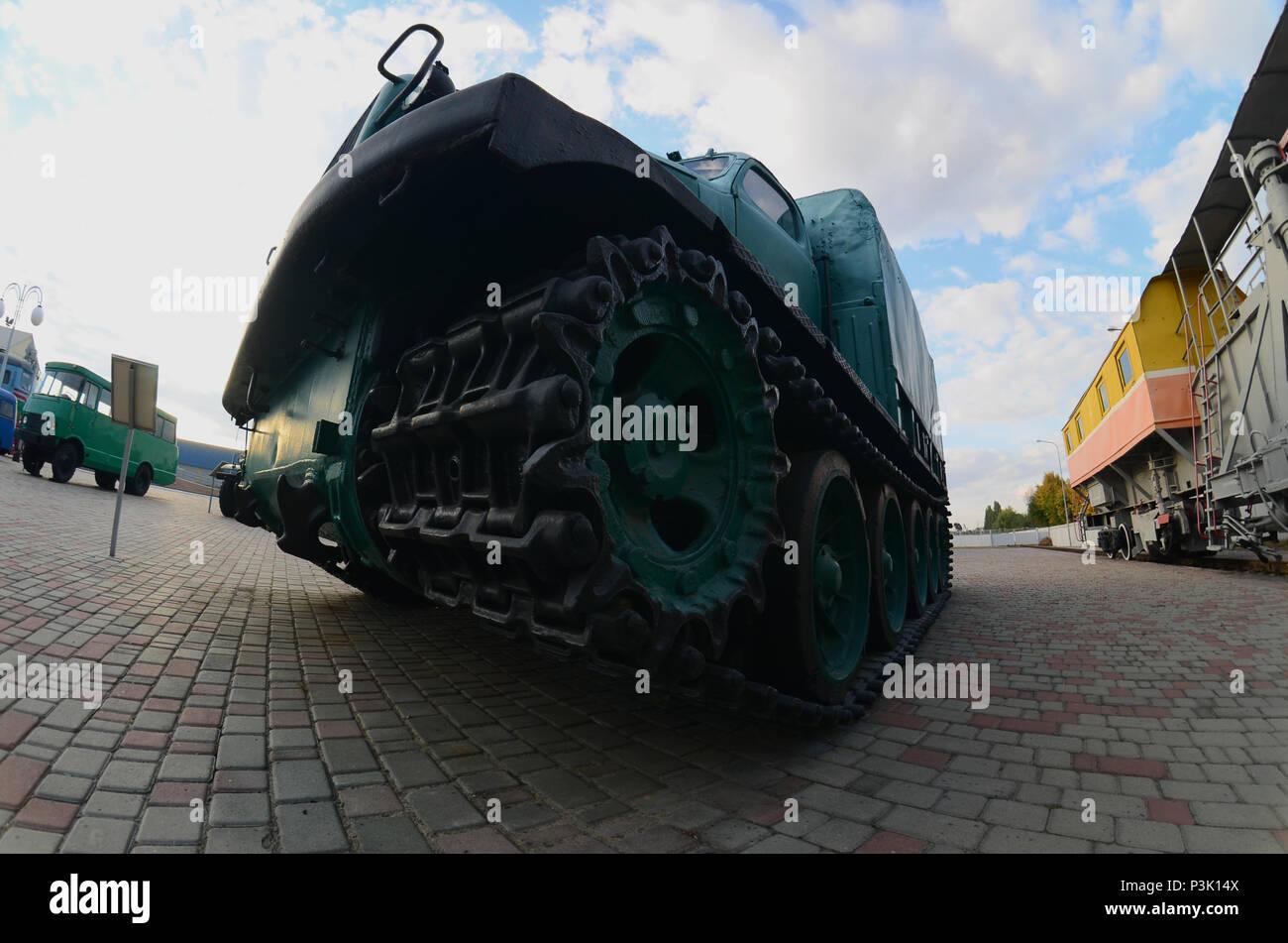 Photo d'une voiture blindée vert russe sur une voie caterpillar parmi les trains de chemin de fer. Une forte distorsion de l'objectif fisheye Banque D'Images