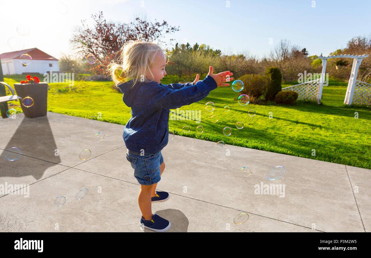 Portrait enfant jouant avec des bulles de savon en plein air Photo Stock