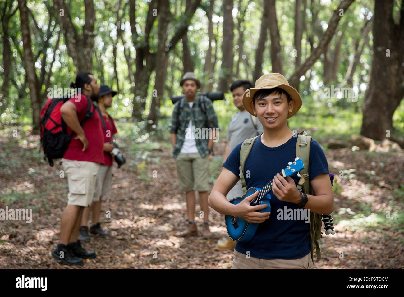 Homme avec ukulele randonnées à la forêt Photo Stock
