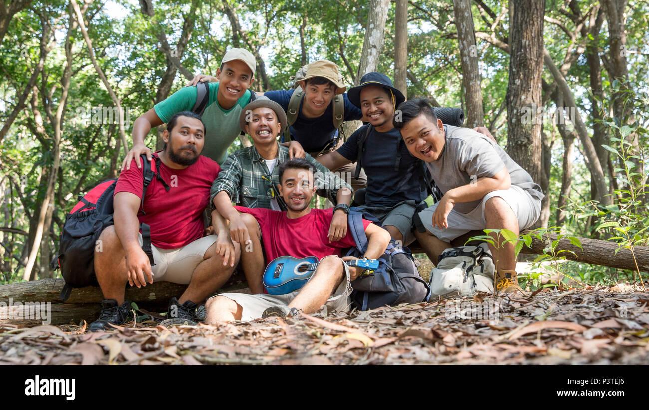 Ami asiatique souriant pour l'appareil photo après la randonnée Photo Stock