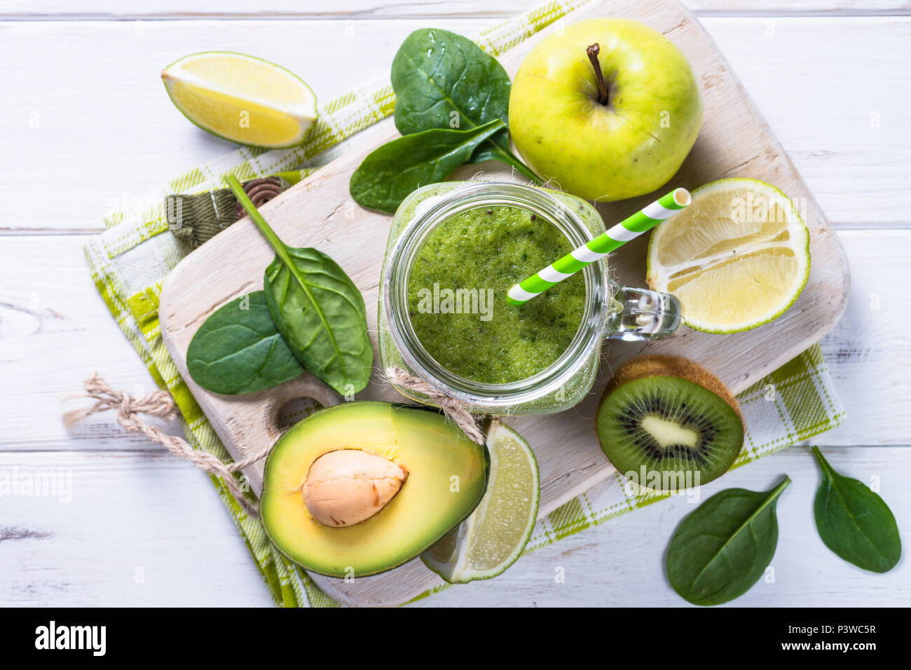 Smoothie vert et d'ingrédients. La chaux, épinards, pommes, kiwi, avocat. Vue de dessus sur table en bois blanc Photo Stock