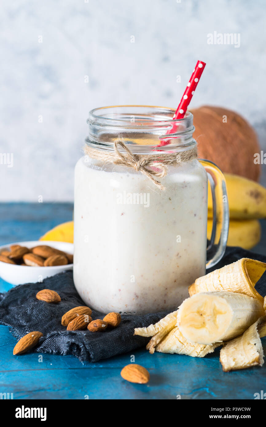Secouer ou de smoothie banane, lait d'amande et noix de coco dans un mug mason. Photo Stock
