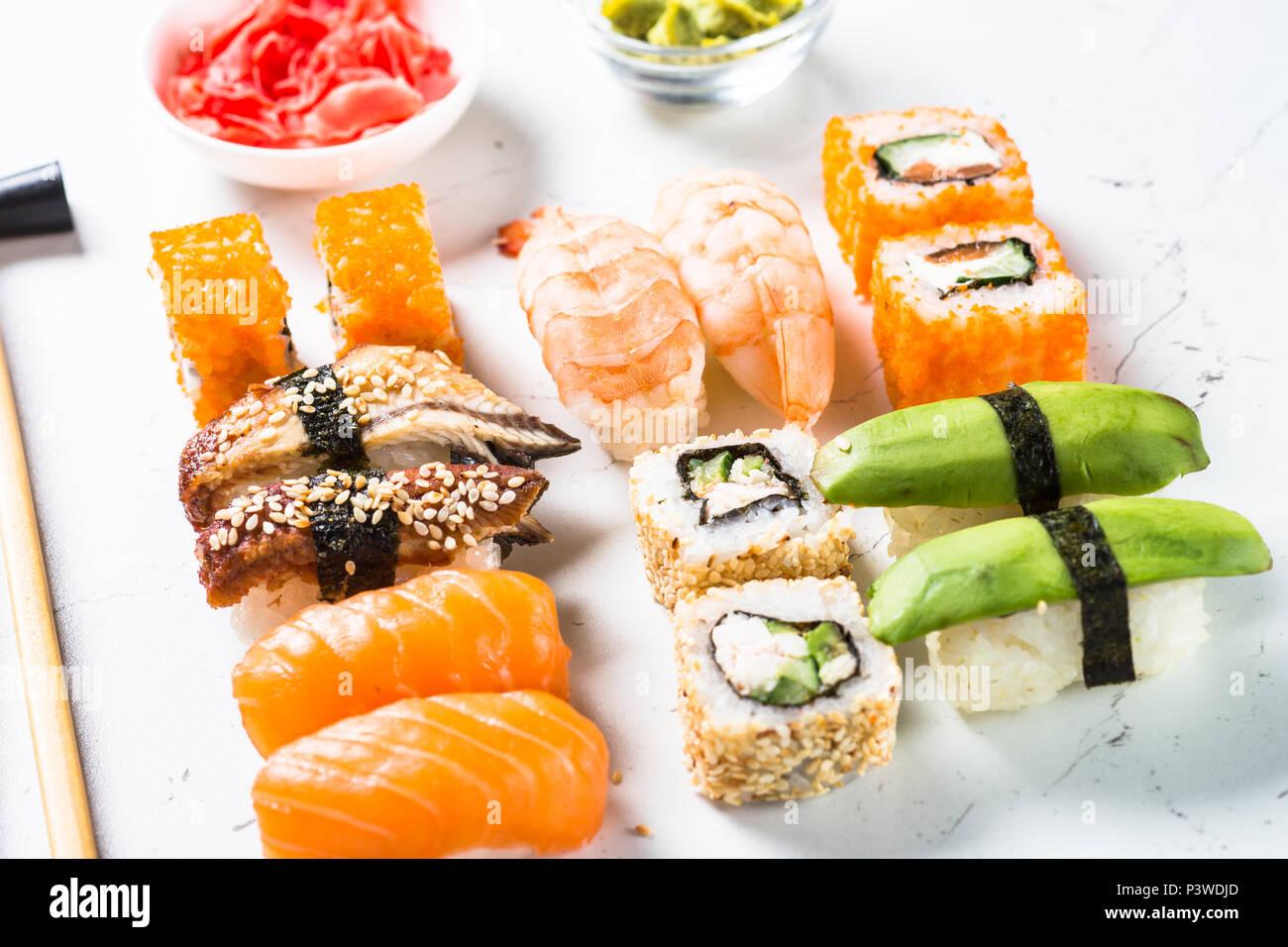 Sushi et sushi roll set sur fond blanc. Cuisine asiatique traditionnelle. Photo Stock