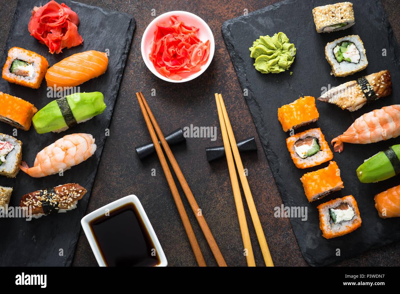 Sushi, maki, nigiri et sushi roll set sur table en pierre sombre vue de dessus. La nourriture japonaise. Photo Stock