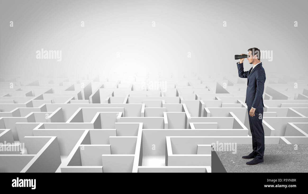 Businessman standing on labyrinthe et regardant vers l'avenir concept Photo Stock
