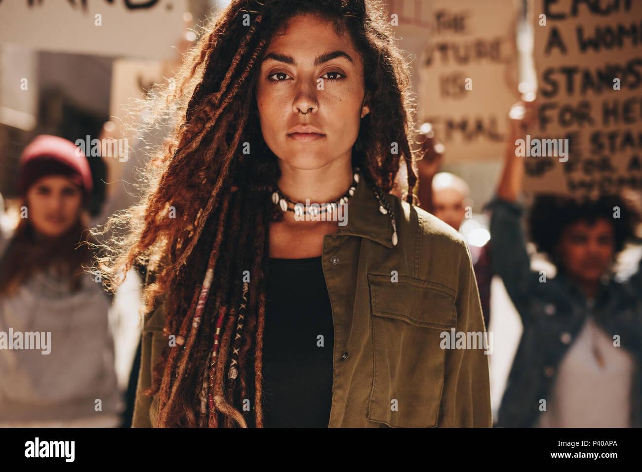 Femme debout à l'extérieur en face de manifestants sur la route. Les femmes qui protestaient avec groupe de militants à l'extérieur. Photo Stock