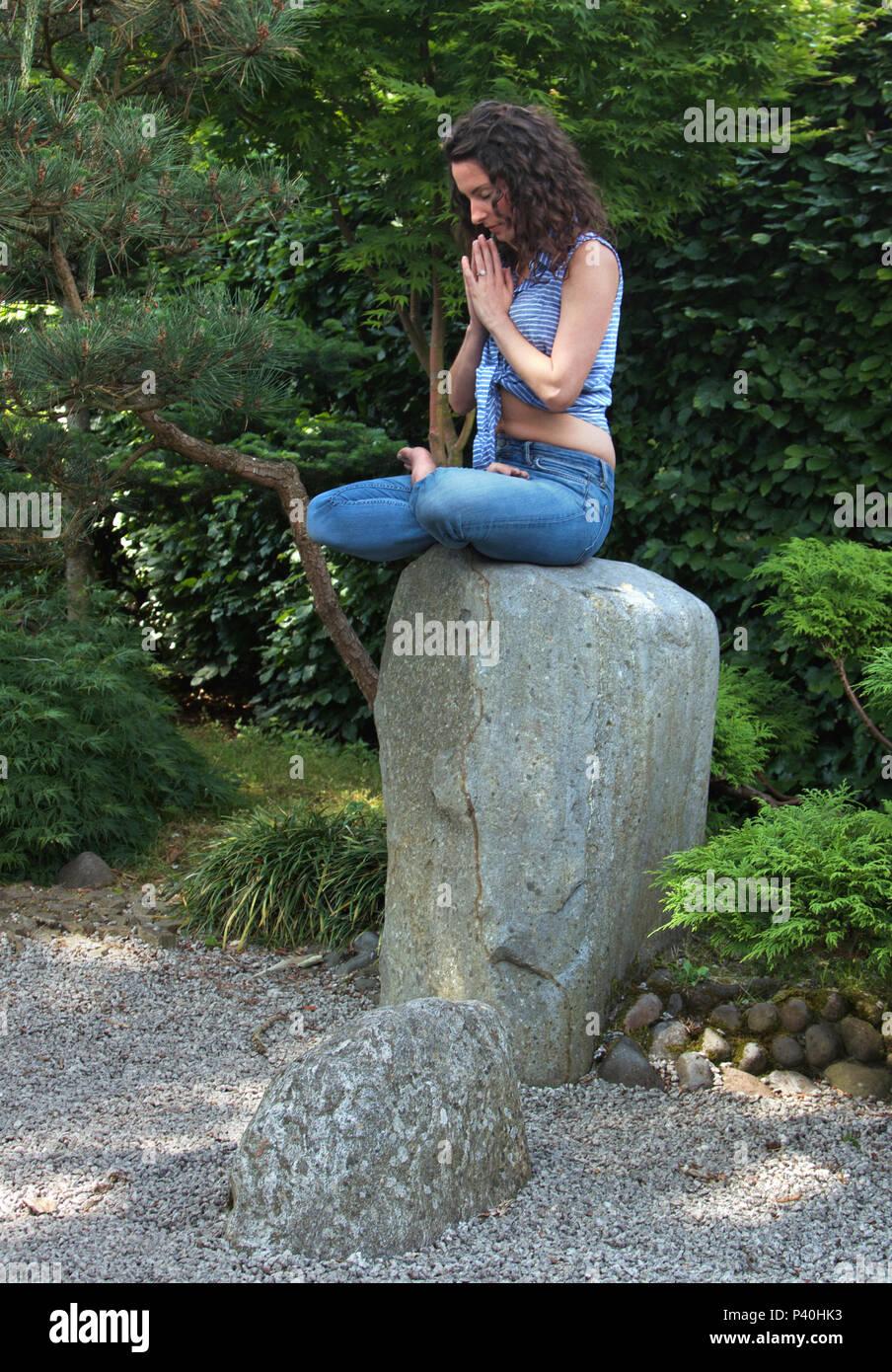 Femme dans la mi-trentaine méditant sur une pierre sacrée Photo Stock