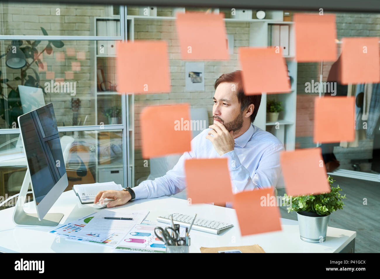 Man working in office derrière une vitre Photo Stock
