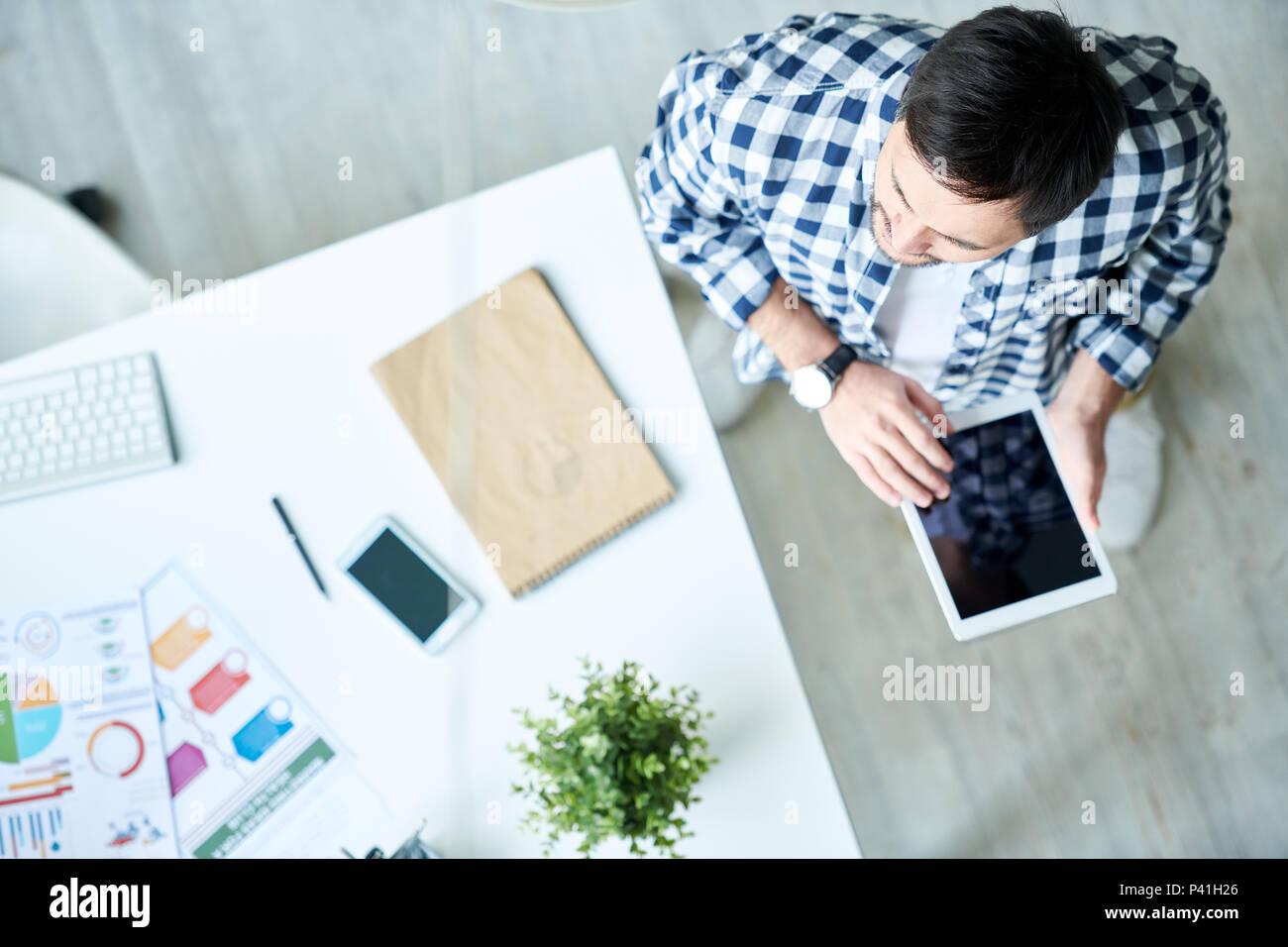 L'homme avec l'espace de travail à tablette Photo Stock