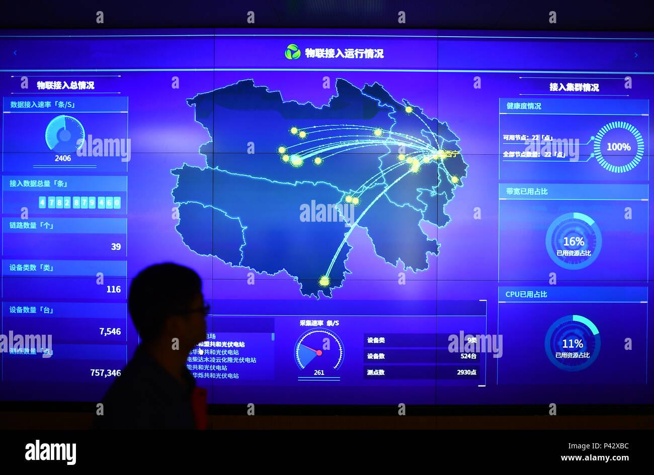 Xining, Province de Qinghai en Chine. 20 Juin, 2018. Un membre du personnel passe devant un écran de données à une nouvelle énergie et de la direction de la big data State Grid Qinghai Electric Power Company à Xining, Province de Qinghai, dans le nord-ouest de la Chine, le 20 juin 2018. La province du Qinghai dans le nord-ouest de la Chine le mercredi a amorcé une période de neuf jours d'alimentation d'énergie propre projet suite à la réussite d'un essai de sept jours l'année dernière. La province prévoit d'utiliser uniquement des sources d'énergie verte pour produire de l'électricité à partir de la chambre 20 au 28 juin pour promouvoir l'utilisation de l'énergie propre. Credit: Zhang Hongxiang/Xinhua/Alamy Live News Photo Stock