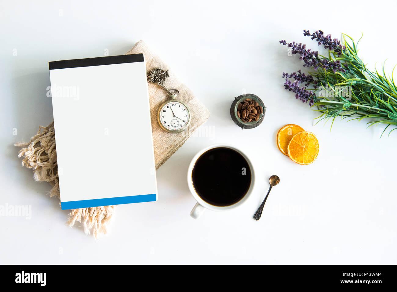 Tasse à café et livre sur table avec des oranges séchées et ancienne montre de poche feuille verte. Le café et le livre sur le tableau blanc avec les grains de café. Coffee Time Photo Stock