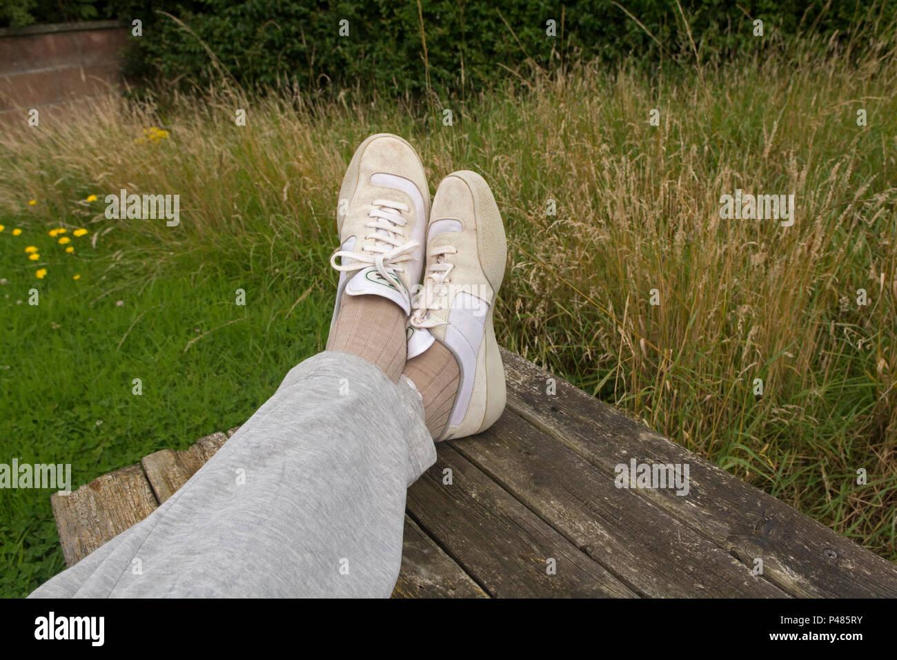 Sports paresseux personne avec des formateurs et des pieds au repos survêtement sur petite table Photo Stock