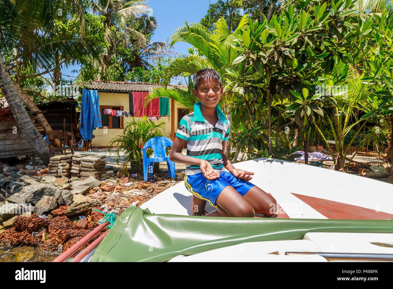 Sri-lankaise locale garçon agenouillé, vivant sur les rives de la rivière tropicale Madu Madu Ganga, les zones humides, au sud-ouest de Sri Lanka Banque D'Images