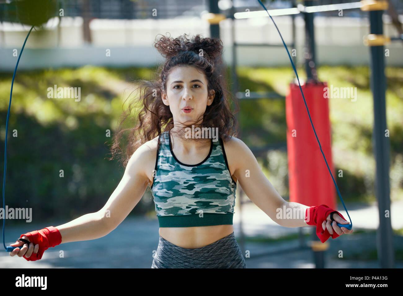 Jeune femme svelte sauter avec une corde, à l'extérieur à l'entraînement de boxe journée ensoleillée Photo Stock