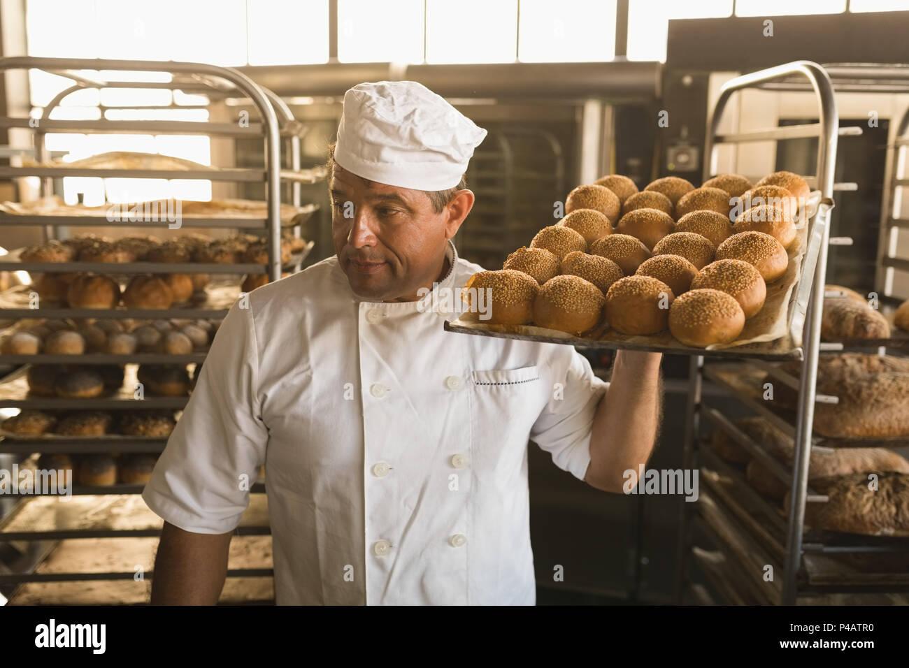 Male baker holding a tray d'aliments sucrés cuits au four Photo Stock