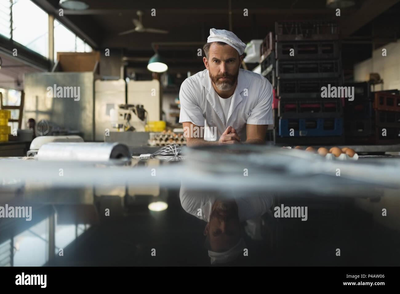 Baker mâle debout dans une boulangerie Photo Stock