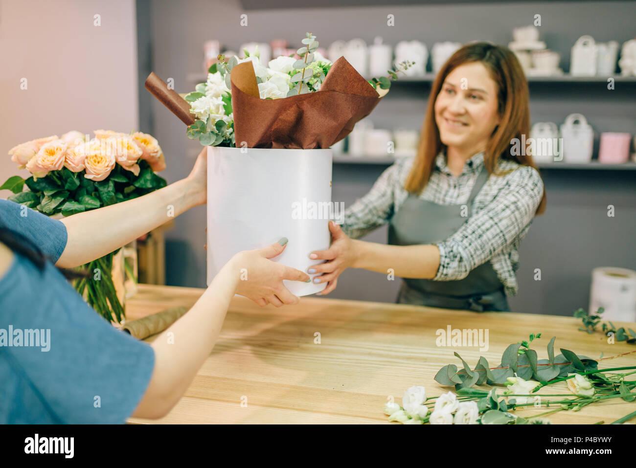 Composition de fleurs fleuriste donne au client Photo Stock