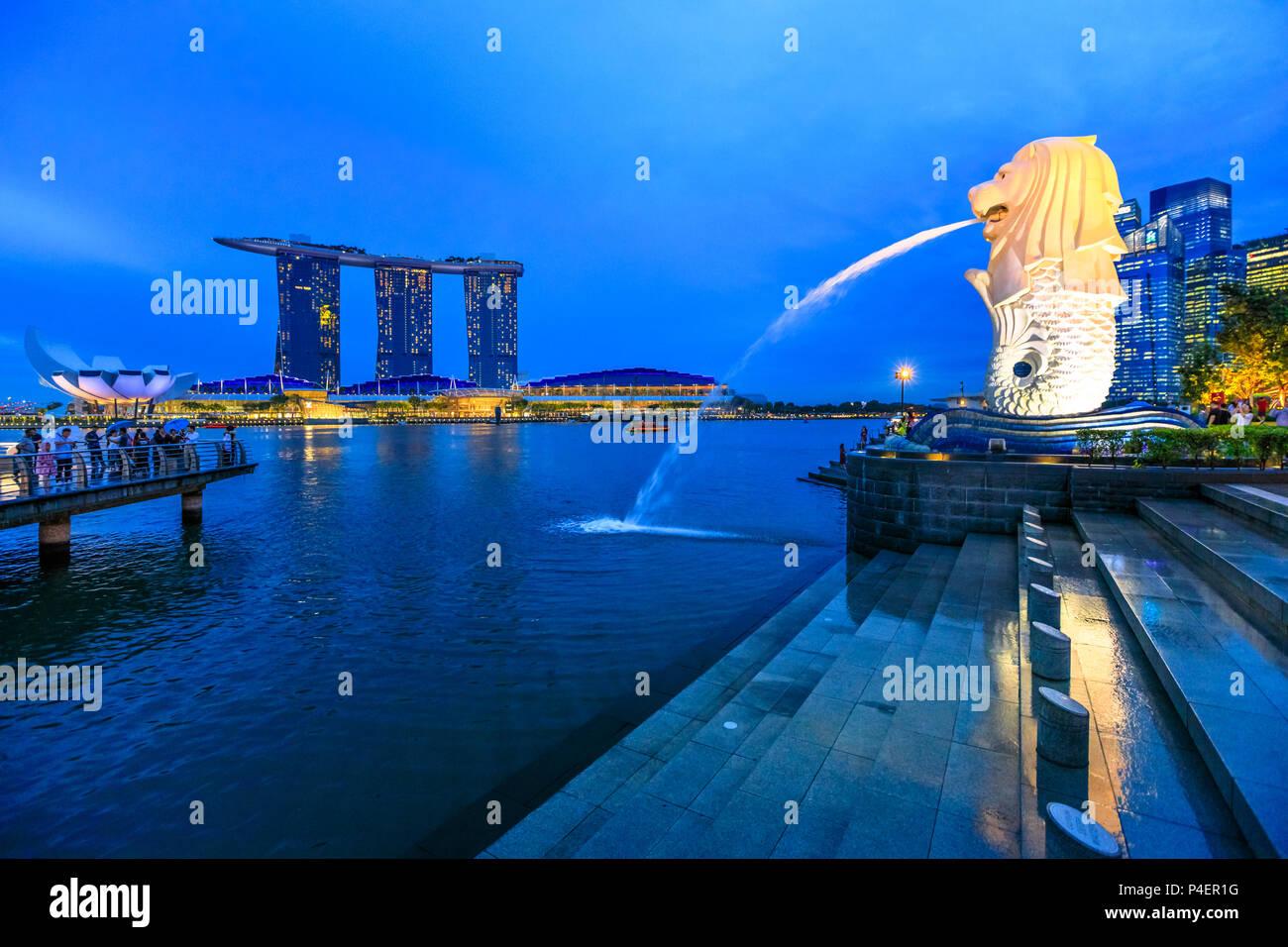 Singapour - Avril 27, 2018: le reflet de l'statue Merlion à Singapour Marina Bay mer. Merlion a une tête de lion et corps de poisson et c'est de l'eau jaillissant de sa bouche. Marina Bay Sands dans les tours d'horizon. Banque D'Images