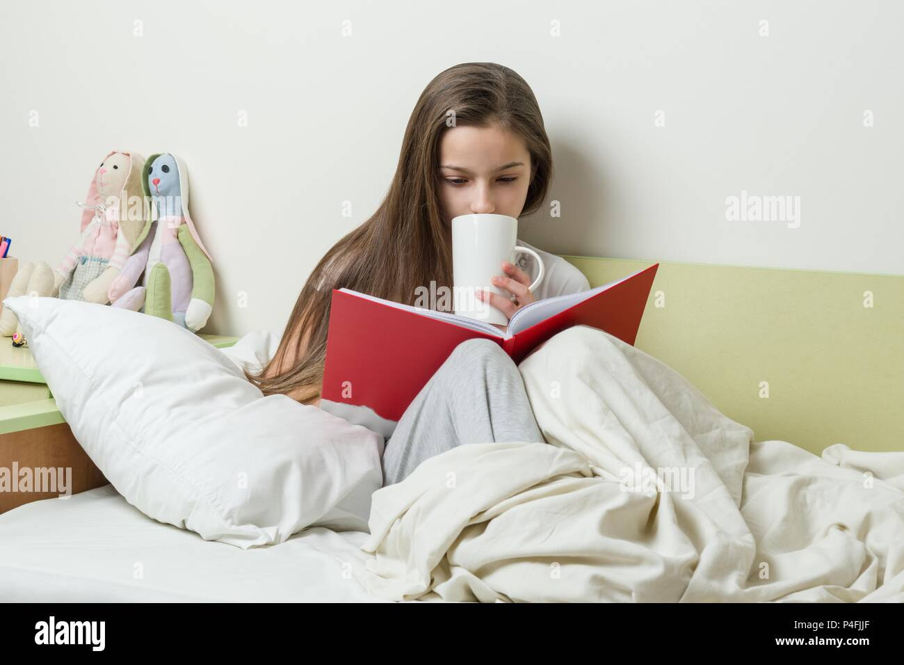 Jeune Fille De 10 Ans En Pyjama Se Lit Livre Et Est