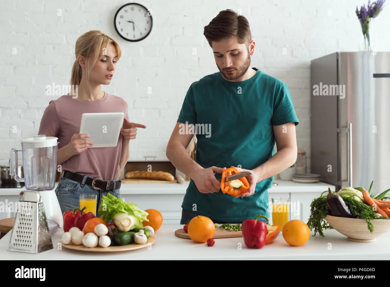 Couple de végétariens à l'aide de tablette avec recette de cuisine Cuisine Photo Stock