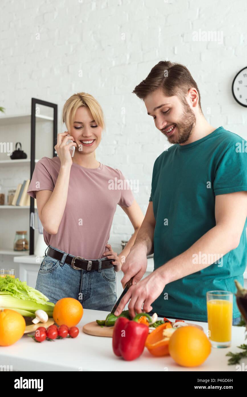 Petite amie vegan parler par smartphone pendant la cuisson à petit ami cuisine Photo Stock