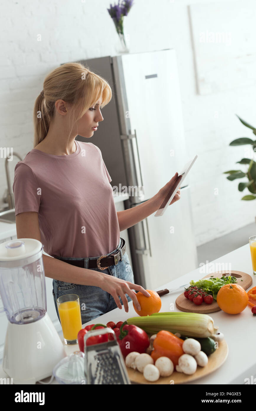 Belle recette vegan girl pour la cuisson sur tablette dans la cuisine Photo Stock