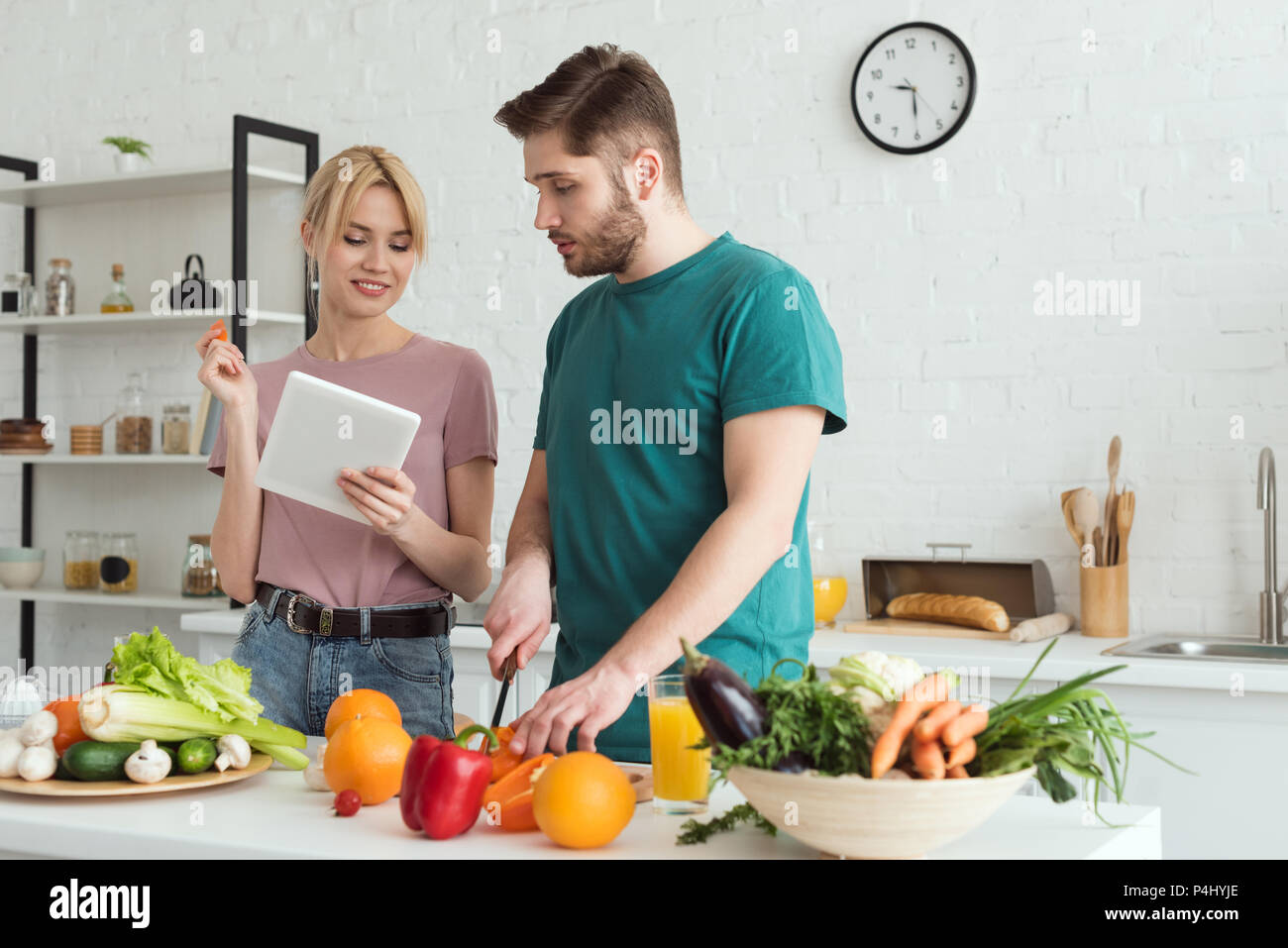 Couple de végétaliens en utilisant comprimé avec recette de cuisine Cuisine Photo Stock