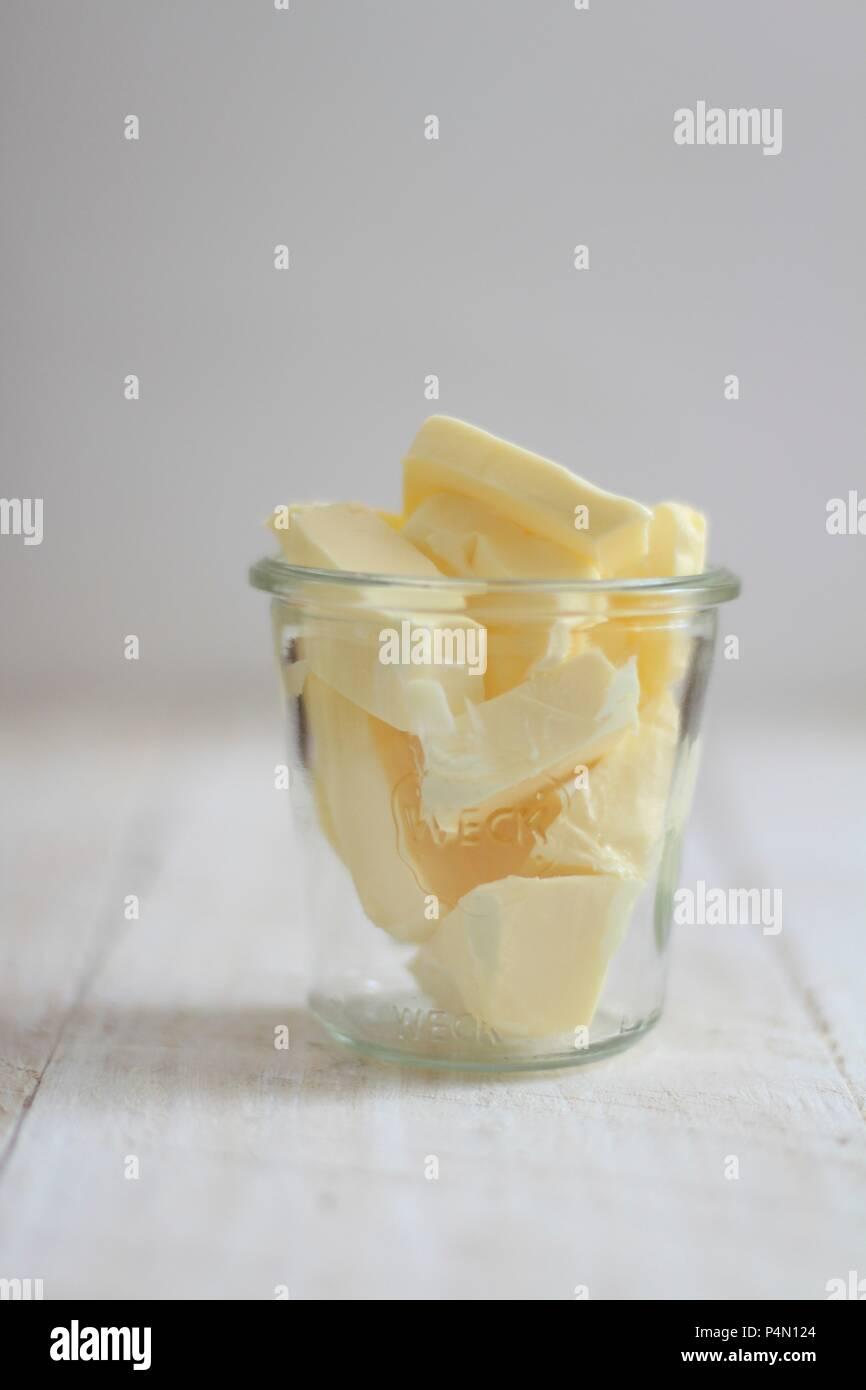 Des morceaux de beurre dans un bocal de verre Photo Stock
