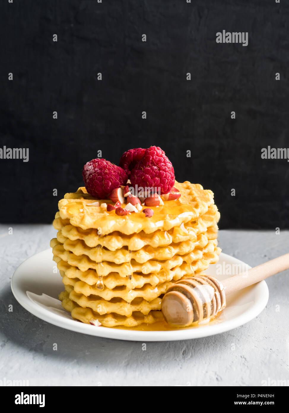 Gaufrettes, biscuits à motifs arrosées de miel à la framboise et d'arachide sur un fond gris mur noir. Photo Stock