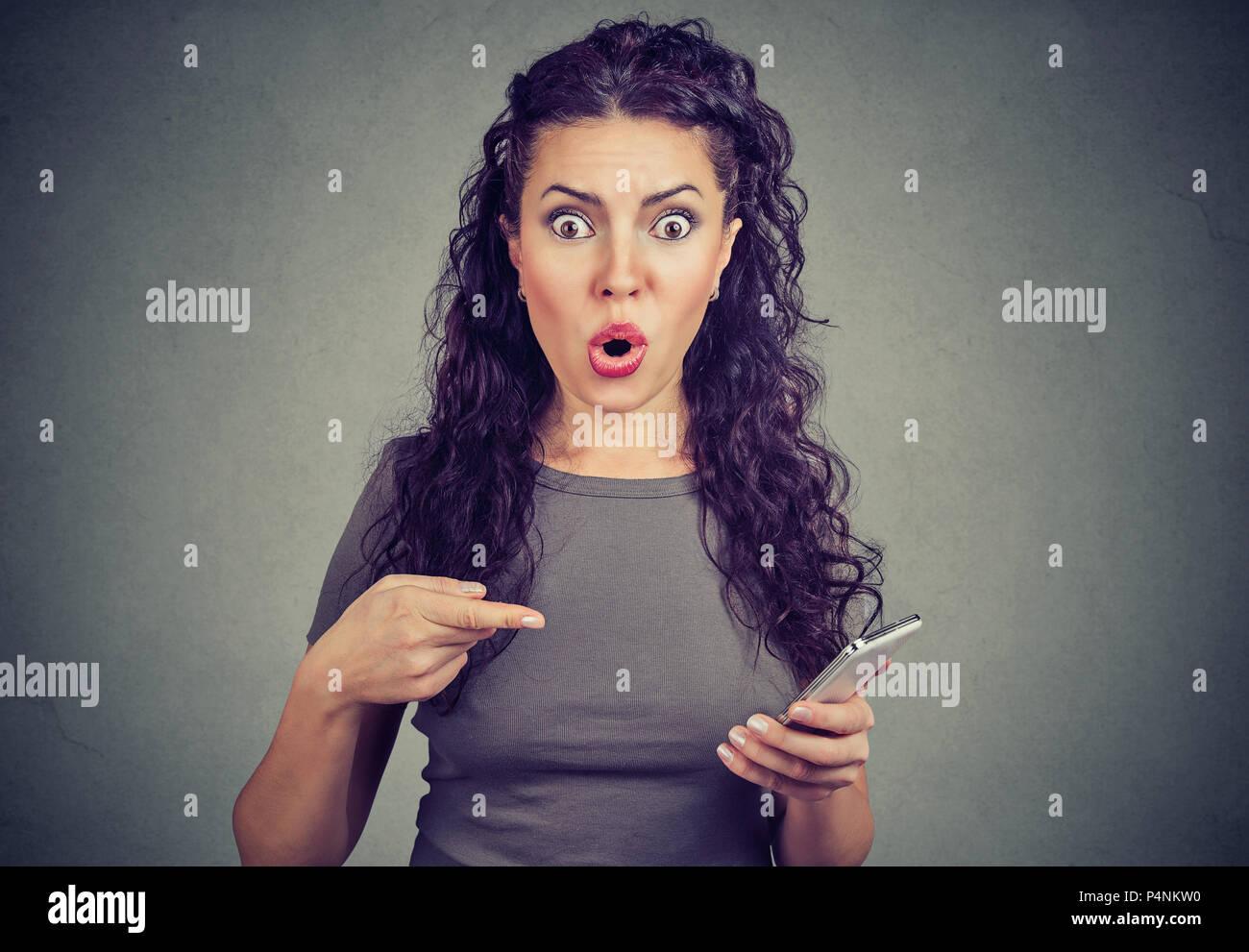Jeune femme à la caméra avec expression terrifiée à pointant sur smart phone, après la lecture de nouvelles bouleversantes sur page web isolé sur fond gris. Photo Stock