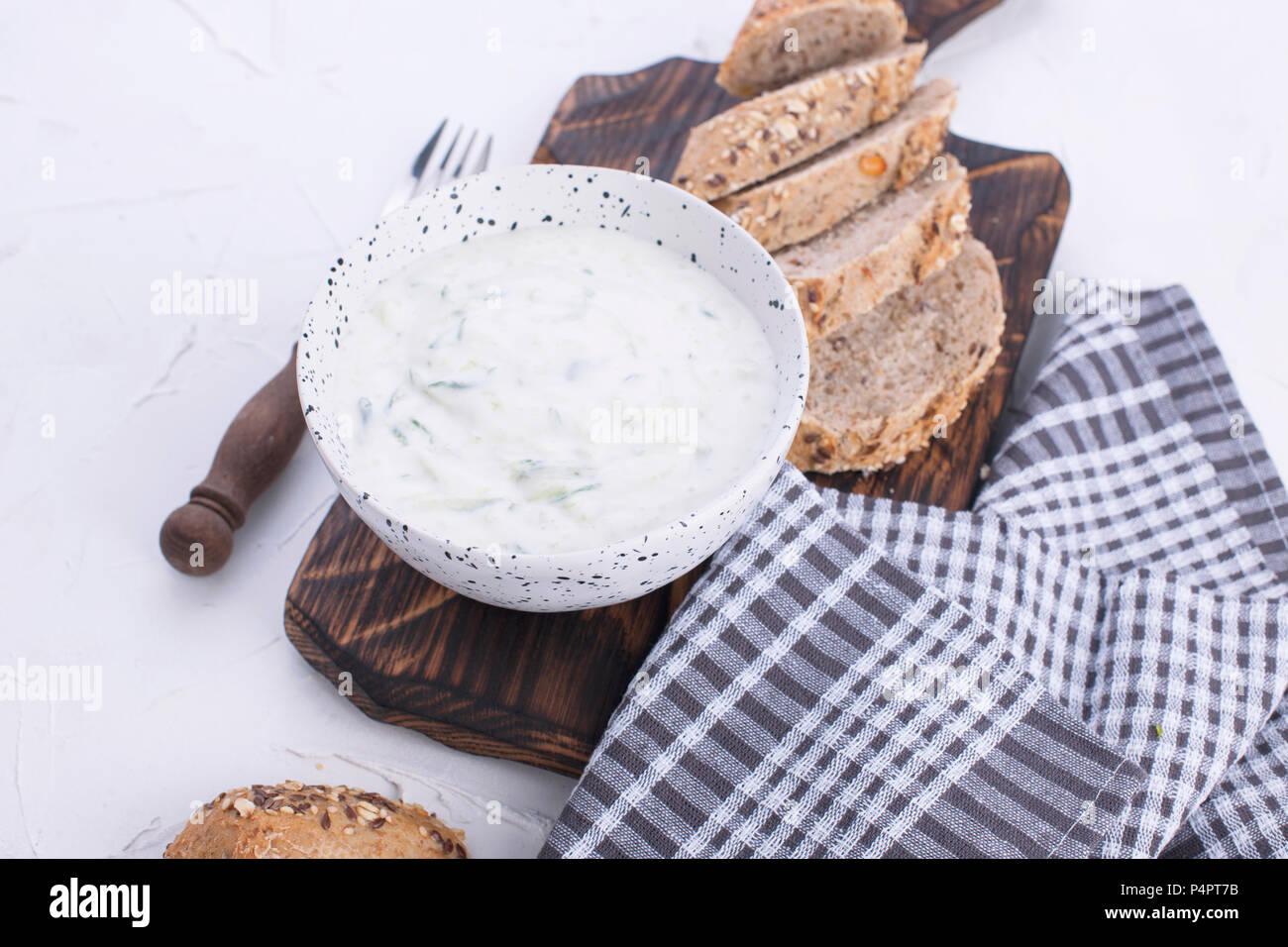 Yaourt au concombre. De dip frais taziki grec célèbre avec le concombre. pain frais, serviette et fond blanc. Copy space Photo Stock