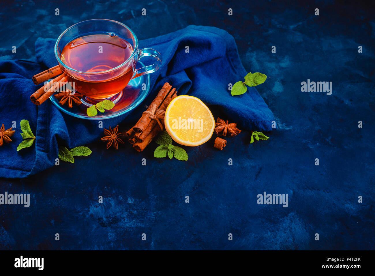 Tasse en verre de thé noir, , nappes, rondelles de citron, la cannelle, l'anis étoile et de feuilles de menthe sur un fond sombre. En-tête de la photographie alimentaire sombre avec l'exemplaire Photo Stock