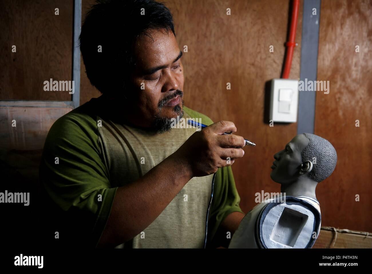 TAYTAY, Rizal, PHILIPPINES - le 21 juin 2018: Un artiste aerographes couleurs pour une statue dans son studio. Photo Stock