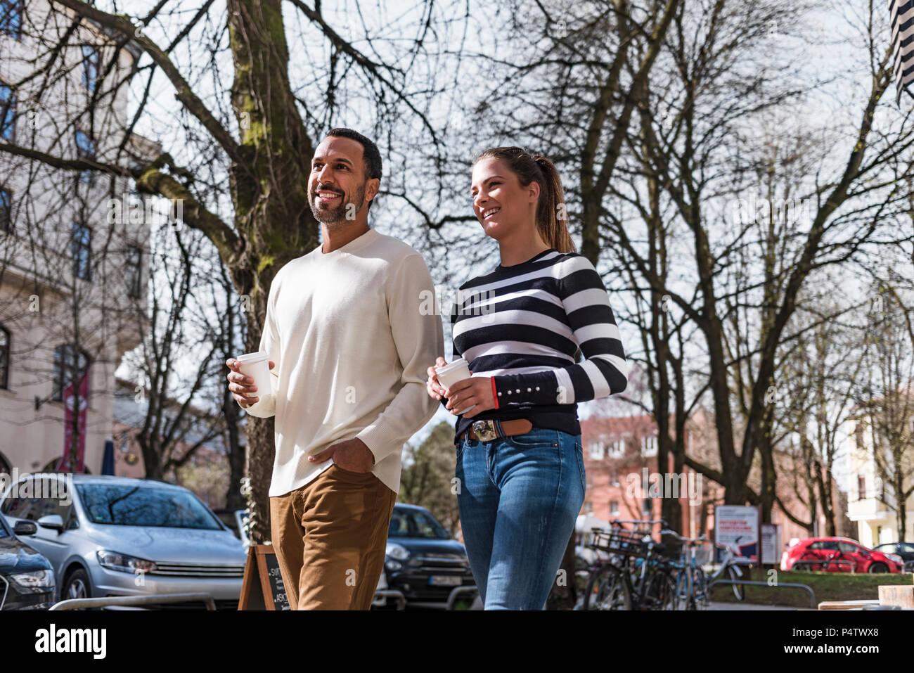 L'homme et de la femme avec des tasses à emporter marcher dans la ville Photo Stock