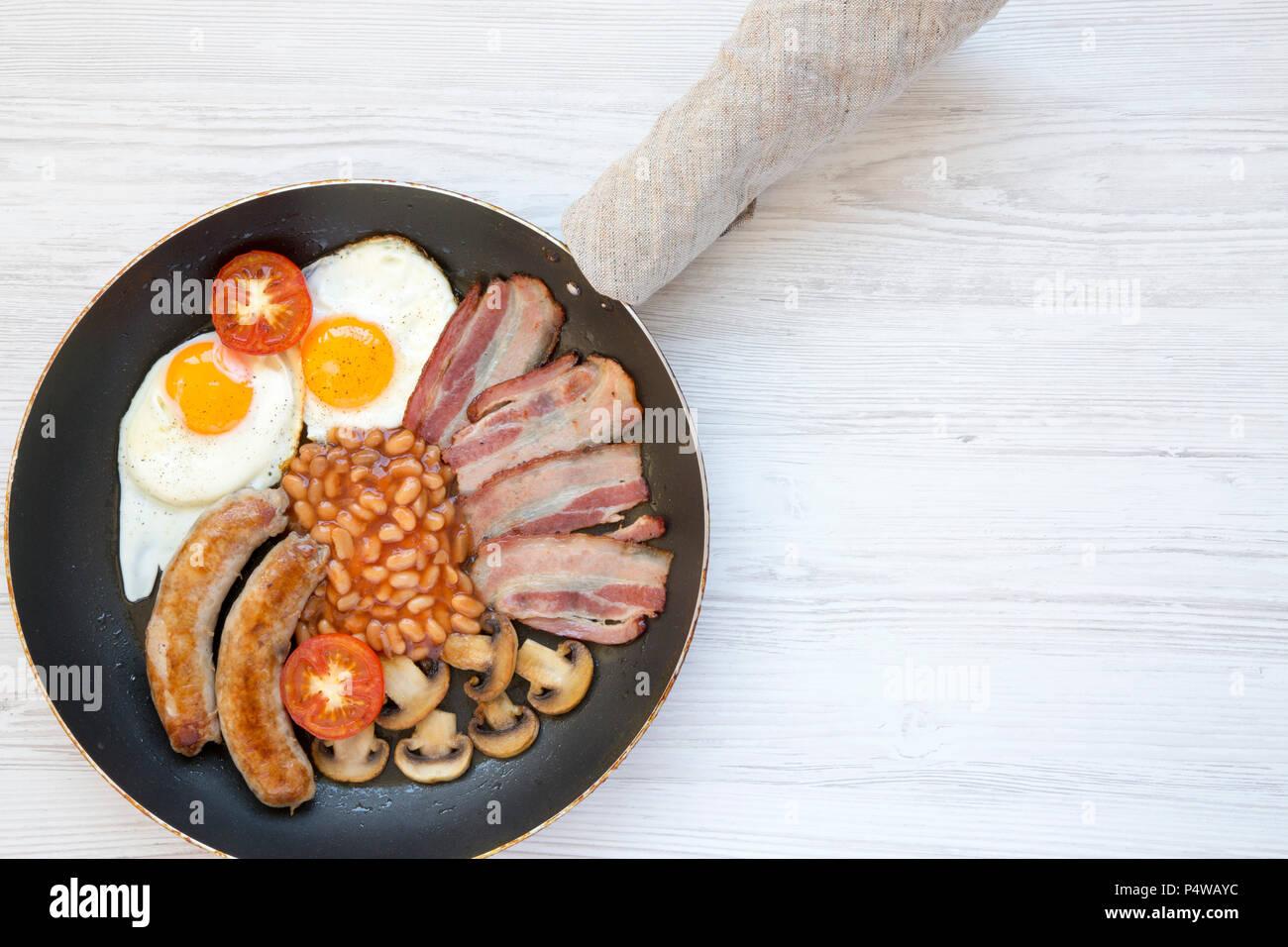 Le petit déjeuner anglais complet dans le moule avec des saucisses, des champignons, des œufs frits, haricots, tomates et bacon sur un fond de bois blanc. Copier l'espace. Vue d'en haut. Location l Banque D'Images