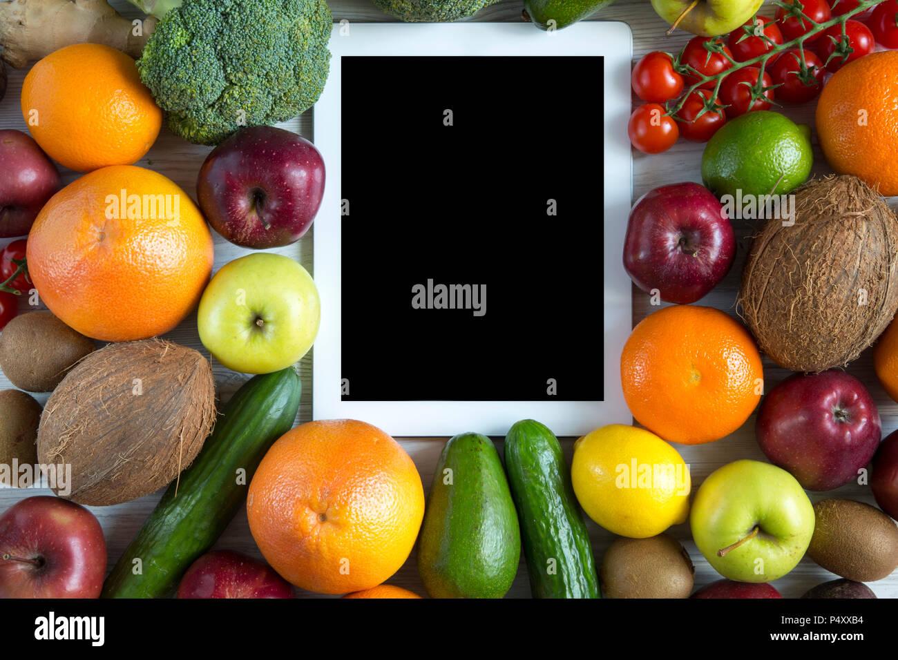 tablette avec cran noir les fruits et l gumes frais biologiques sur fond de bois blanc la. Black Bedroom Furniture Sets. Home Design Ideas