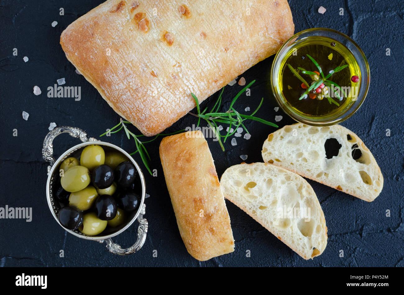 Tranches de pain fraîchement cuit au four traditionnel de pain italien pain ciabatta sur noir table de pierre avec le romarin, le sel, l'huile d'olive et d'olives. Concept de cuisine italienne. Photo Stock