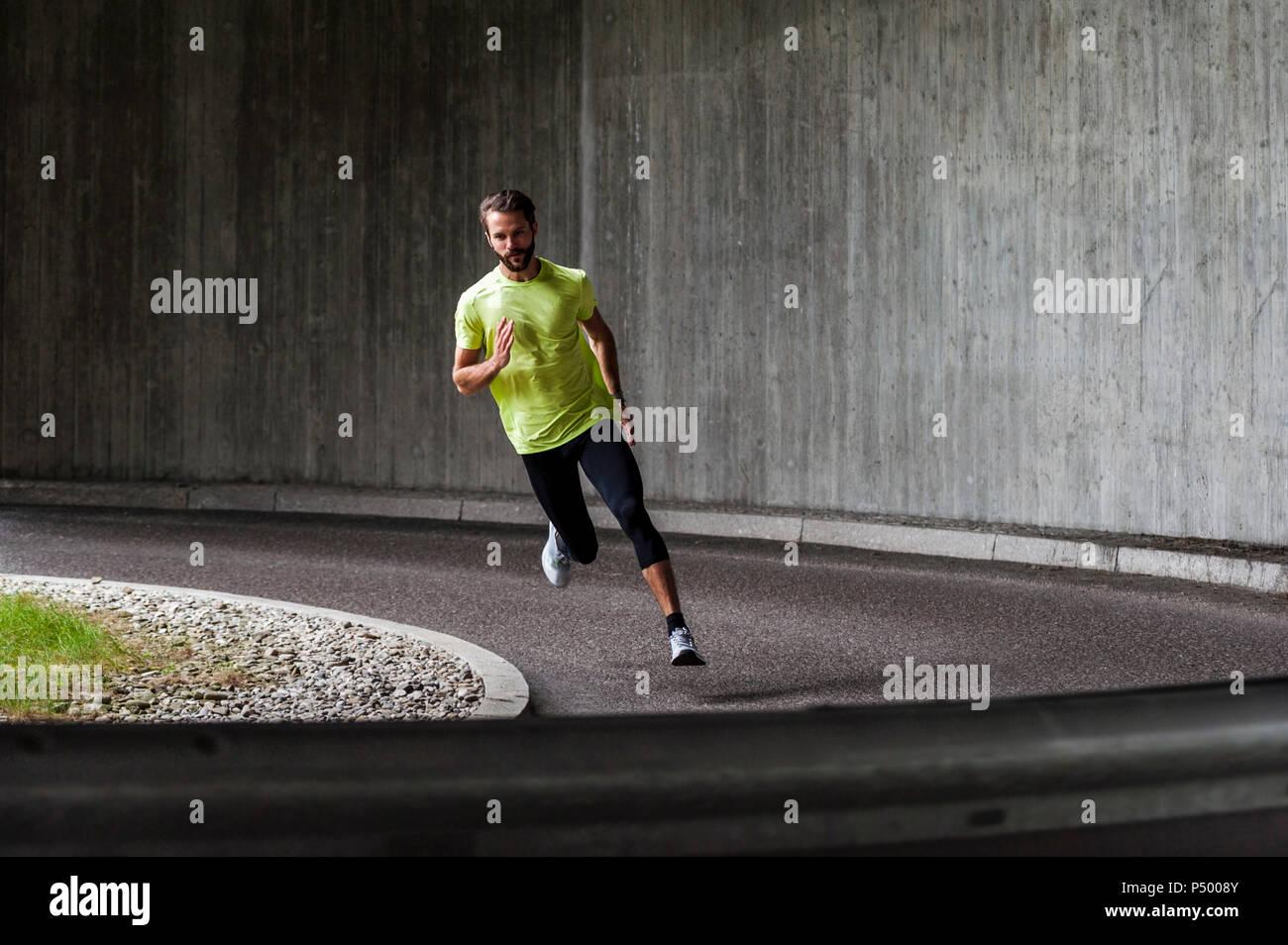 Homme qui court dans une rue d'une courbe Photo Stock