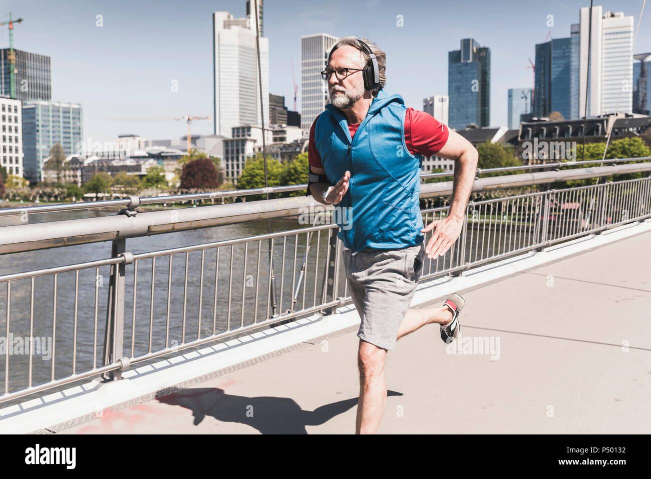 Homme mûr avec des écouteurs d'exécution sur pont dans la ville Photo Stock